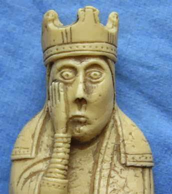 ivory chess piece with hand on face, looking astounded